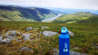 Scottish Water blue bottle on top of scenic hill